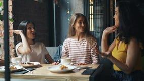 Lyckliga kvinnliga vänner som talar därefter att göra som är högt-fem, och att skratta i modernt kafé stock video