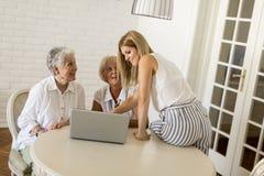 Lyckliga kvinnor av tre utvecklingar i livingroom med bärbara datorn Royaltyfri Bild