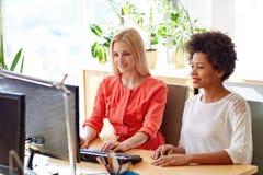 Lyckliga kvinnor eller studenter med datoren i regeringsställning Royaltyfri Bild
