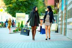 Lyckliga kvinnor går gatan med shopping hänger lös royaltyfri bild