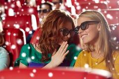 Lyckliga kvinnor i exponeringsglas som 3d håller ögonen på film på bion Royaltyfri Foto