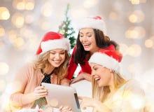 Lyckliga kvinnor i santa hjälpredahattar med minnestavlaPC Royaltyfri Bild