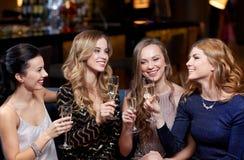 Lyckliga kvinnor med champagneexponeringsglas på nattklubben Royaltyfri Foto