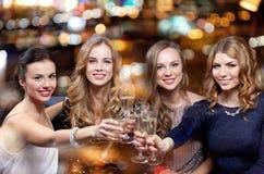 Lyckliga kvinnor med champagneexponeringsglas på nattklubben Fotografering för Bildbyråer