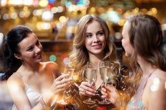 Lyckliga kvinnor med champagneexponeringsglas på nattklubben Arkivbilder