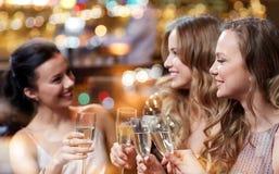Lyckliga kvinnor med champagneexponeringsglas på nattklubben Royaltyfria Foton