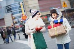 Lyckliga kvinnor med gåvor och shoppingpåsar som går på stadsgatan under vinter Arkivbild