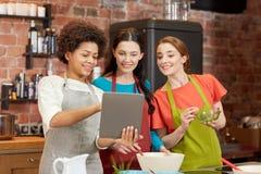 Lyckliga kvinnor med minnestavlaPC som lagar mat i kök Arkivfoton