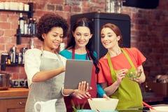Lyckliga kvinnor med minnestavlaPC som lagar mat i kök Fotografering för Bildbyråer