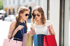 Lyckliga kvinnor med shoppingpåsar i stad Fotografering för Bildbyråer