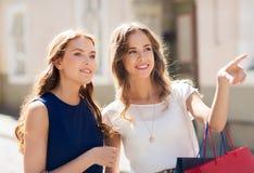 Lyckliga kvinnor med shoppingpåsar i stad Royaltyfri Bild