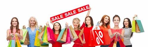 Lyckliga kvinnor med shoppingpåsar och försäljningstecknet royaltyfria bilder