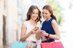 Lyckliga kvinnor med shoppingpåsar och smartphonen Fotografering för Bildbyråer