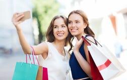 Lyckliga kvinnor med shoppingpåsar och smartphonen Royaltyfria Bilder