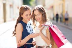 Lyckliga kvinnor med shoppingpåsar och smartphonen Arkivfoto