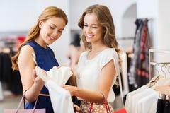 Lyckliga kvinnor med shoppingpåsar på kläder shoppar Royaltyfri Fotografi