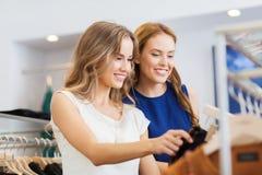Lyckliga kvinnor med shoppingpåsar på kläder shoppar Fotografering för Bildbyråer