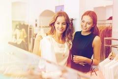 Lyckliga kvinnor med shoppingpåsar på kläder shoppar Arkivfoton