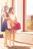 Lyckliga kvinnor med shoppingpåsar på shoppar fönstret Arkivfoton