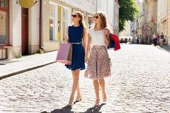 Lyckliga kvinnor med shoppingpåsar som går i stad arkivfoto