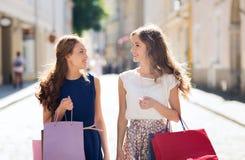Lyckliga kvinnor med shoppingpåsar som går i stad Royaltyfri Fotografi