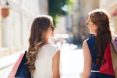 Lyckliga kvinnor med shoppingpåsar som går i stad Royaltyfria Foton