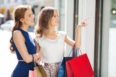Lyckliga kvinnor med shoppingpåsar på shoppar fönstret Royaltyfri Bild
