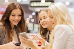 Lyckliga kvinnor med smartphones och minnestavlaPC i galleria Royaltyfri Foto