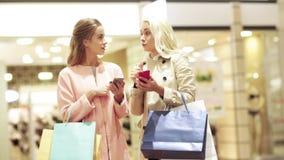 Lyckliga kvinnor med smartphones och shoppingpåsar lager videofilmer