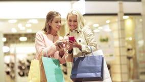Lyckliga kvinnor med smartphones och shoppingpåsar arkivfilmer