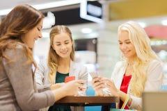 Lyckliga kvinnor med smartphones och shoppingpåsar Royaltyfri Fotografi