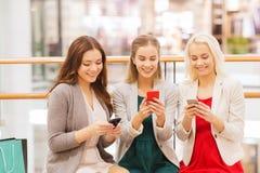 Lyckliga kvinnor med smartphones och shoppingpåsar Royaltyfri Bild