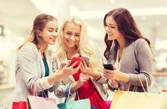 Lyckliga kvinnor med smartphones och shoppingpåsar Royaltyfri Foto