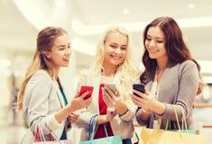 Lyckliga kvinnor med smartphones och shoppingpåsar Arkivbild