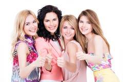 Lyckliga kvinnor med tummar up tecknet Arkivbild