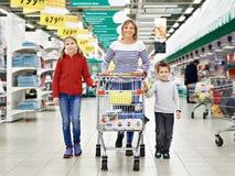 Lyckliga kvinnor och barn med vagnsshopping Royaltyfri Foto