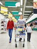 Lyckliga kvinnor och barn med vagnsshopping Arkivfoton