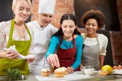 Lyckliga kvinnor och kocken lagar mat bakning i kök Arkivbild