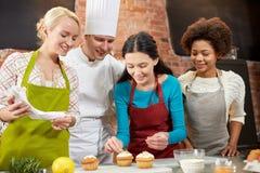 Lyckliga kvinnor och kocken lagar mat bakning i kök Royaltyfri Fotografi