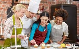 Lyckliga kvinnor och kocken lagar mat matlagning i kök Arkivbild