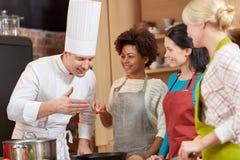 Lyckliga kvinnor och kocken lagar mat matlagning i kök Arkivbilder