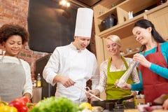 Lyckliga kvinnor och kocken lagar mat matlagning i kök royaltyfri fotografi