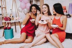 Lyckliga kvinnor som äter kakan som firar dag för kvinna` s royaltyfria foton