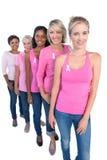 Lyckliga kvinnor som bär rosa färger och band för bröstcancer Royaltyfri Bild