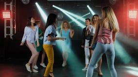 Lyckliga kvinnor som dansar till musiken av partiet med hennes andra flickavänner på dansgolvet av en trendig nattklubb in stock video