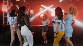 Lyckliga kvinnor som dansar till musiken av partiet med hennes andra flickavänner på dansgolvet av en trendig nattklubb in arkivfilmer