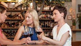 Lyckliga kvinnor som dricker rött vin på stången eller restaurangen arkivfilmer