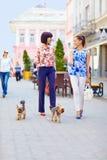 Lyckliga kvinnor som går hundkapplöpningen på stadsgatan Royaltyfri Bild