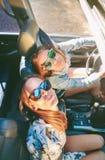 Lyckliga kvinnor som har gyckel inom av cabrioletbilen Arkivfoto