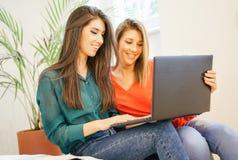 Lyckliga kvinnor som hemma använder datoranteckningsboken i ungdomarför vardagsrum som - surfar på den hållande ögonen på videoen arkivbild